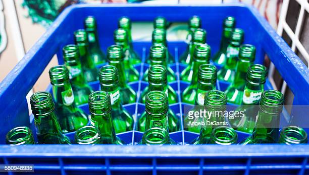 Empty green bottles in a blue crate