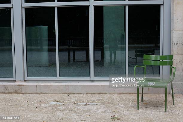 Empty green chair in front of built structure