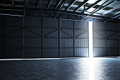 Empty building hanger with the door cracked open with room for text or copy space.Photo realistic rendering