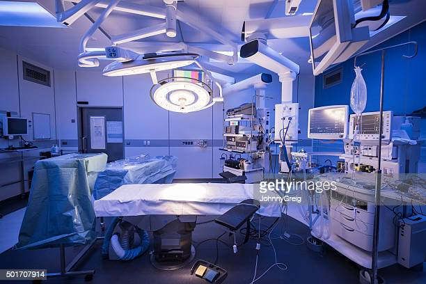 Empty hospital operating theatre with lighting over bed
