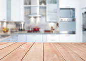 Empty kitchen wood countertop with defocused modern kitchen background