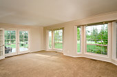 Carpetted empty living room with large bay windows.
