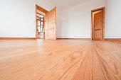 Empty living room with brown wooden floor