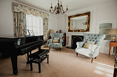 A traditional looking music room with armchairs and a grand piano.