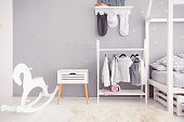 Empty nursery room with clear wall, nightstand, toys and wooden horse