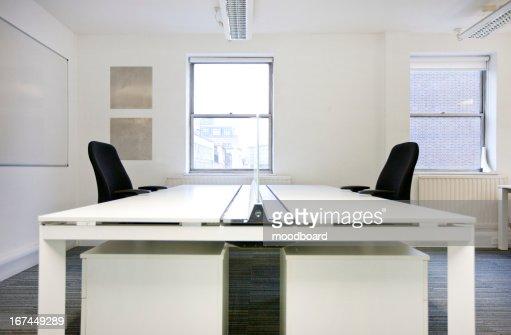 Empty office desks back to back : Stock Photo