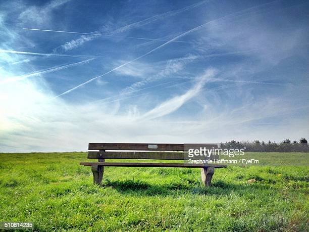 Empty park bench in field