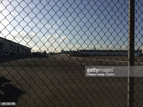 Empty Parking Lot Against Sky Seen Through Chainlink Fence