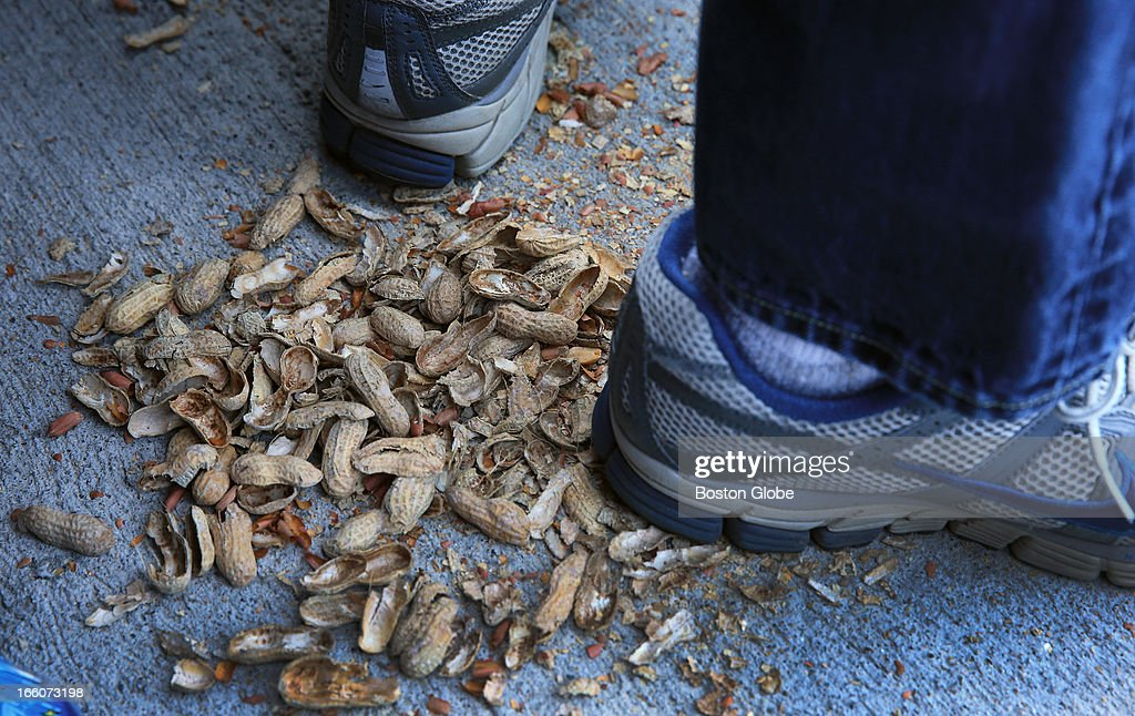 Empty peanut shells beneath the shoes of Rob McMorrow from Concord. The Baltimore Orioles play the Boston Red Sox during Opening Day at Fenway Park.