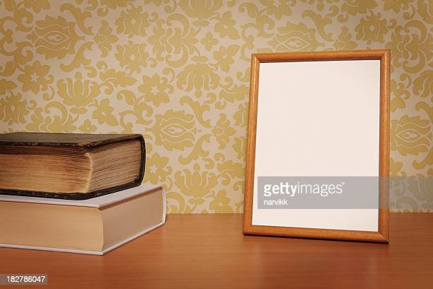 Empty Photo Frame and Books on the Table