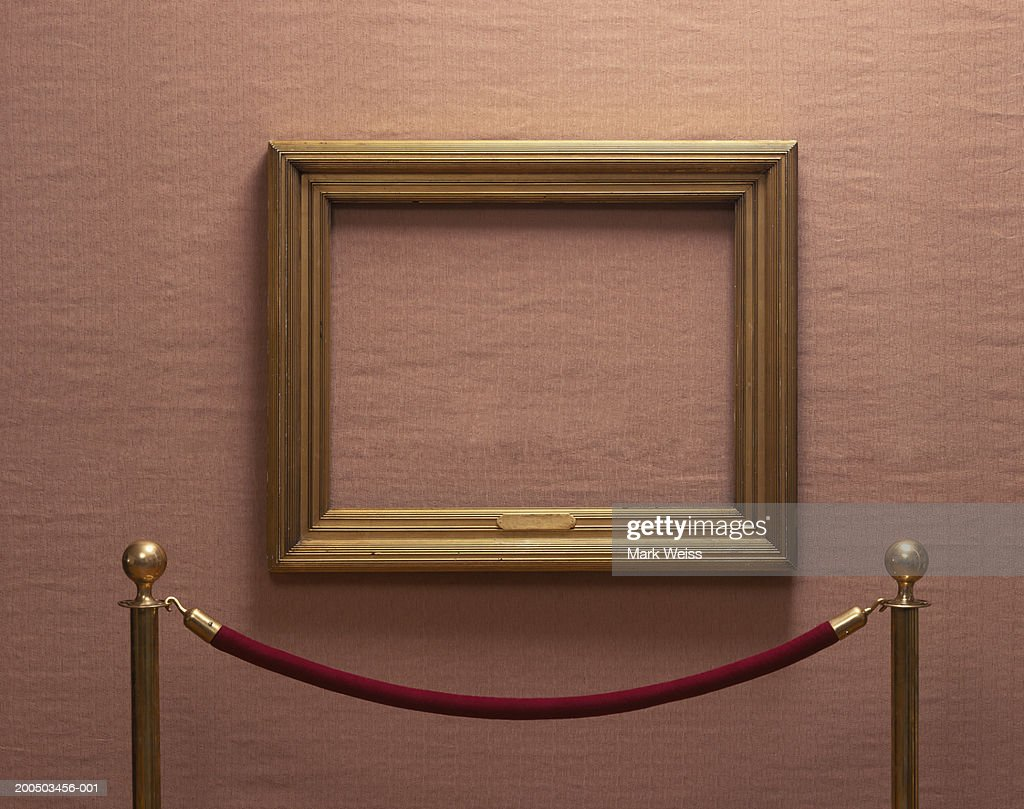 Empty picture frame behind rope barrier : Stock Photo