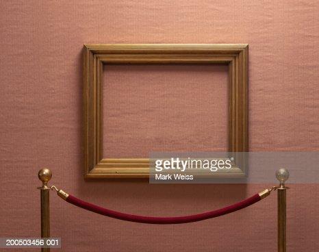 Empty picture frame behind rope barrier : Bildbanksbilder