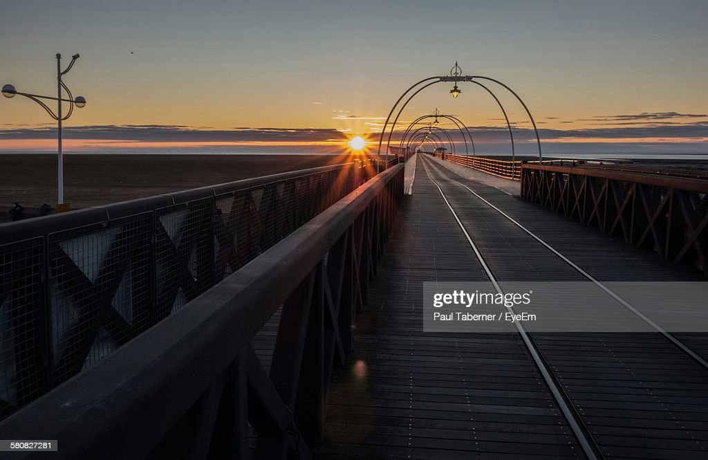 Empty Pier At Beach Against Sky During Sunset