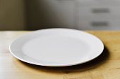 closeup of an empty white ceramic plate on a modern wooden table or countertop