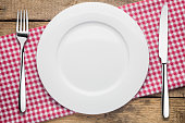 empty plate on a wooden background, a napkin in a red and white cage, a fork a knife