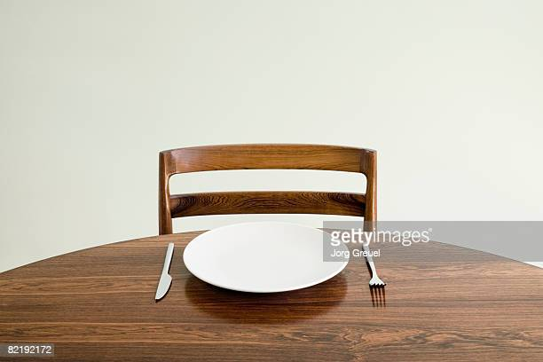 Empty plate with knife and fork on table
