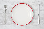 Empty red striped plate with table knife and fork on white wooden kitchen table.