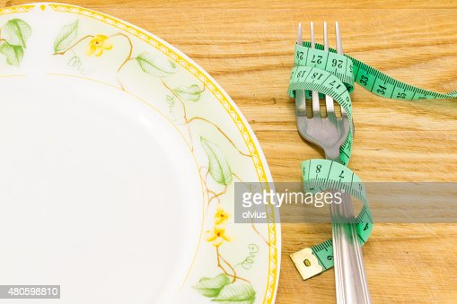 Empty plate with measure tape : Stock Photo
