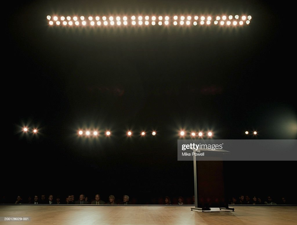 Empty podium on stage, audience in background