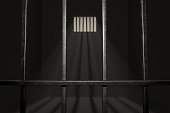 Empty prison cell. Light rays shining through window in jail. 3D rendered illustration.