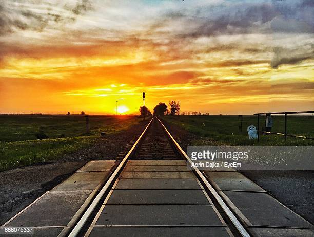 Empty Railroad Track Against Cloudy Sky During Sunset