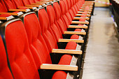 Oblique view over a row of red theatre seats at a movie theatre