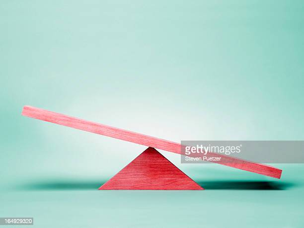 Empty red seesaw on green background