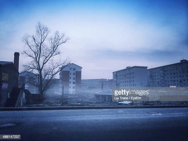 Empty road against bare tree and buildings