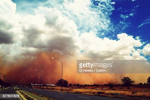 Empty Road Against Sandstorm In Background