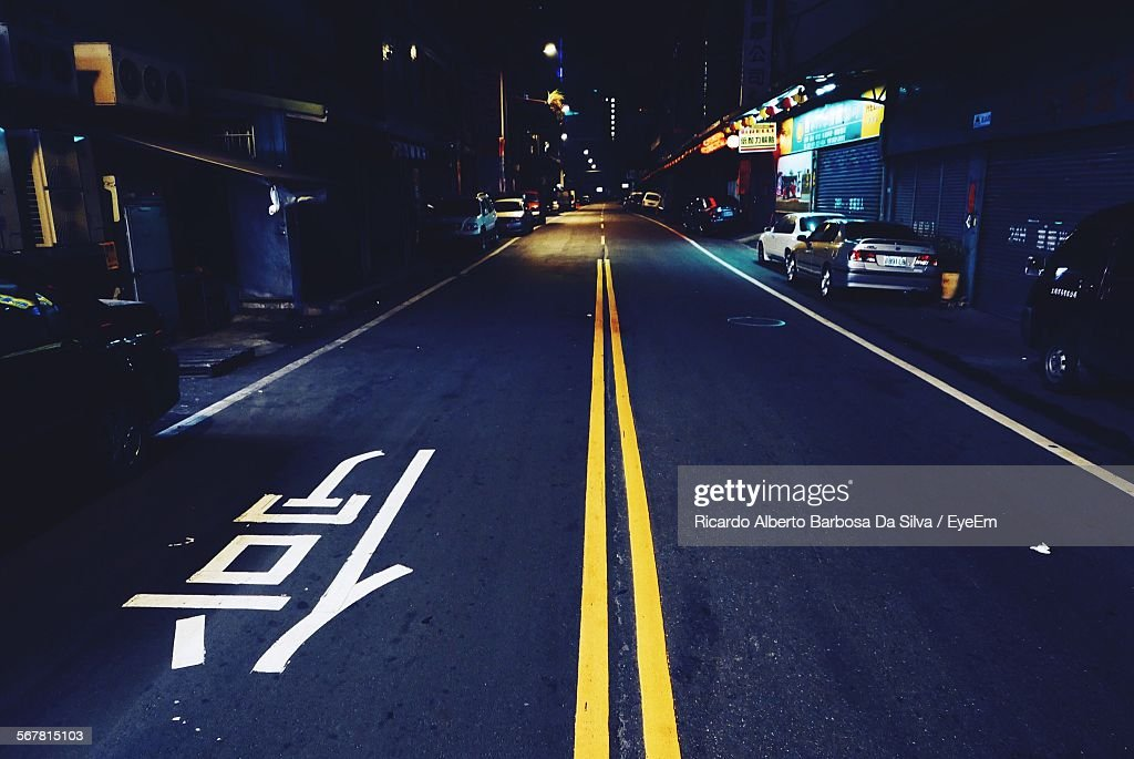 Empty Road Along Built Structures At Night