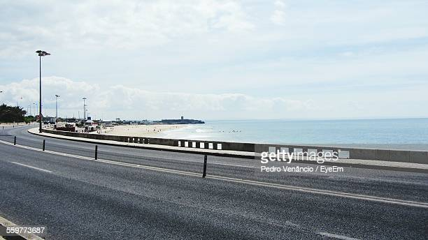 Empty Road Along Calm Sea Against Sky