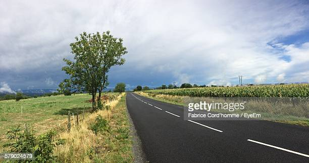 Empty Road Amidst Field Against Cloudy Sky
