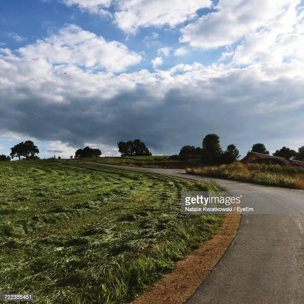 Empty Road By Grassy Field Against Cloudy Sky