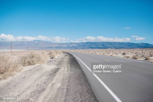 Empty Road By Landscape Against Blue Sky