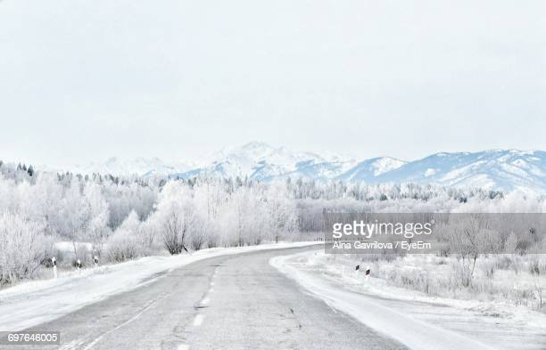 Empty Road Passing Through Snow Covered Mountains