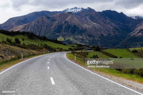 Empty road to mountains in remote landscape, Wanaka, Central Otago, New Zealand