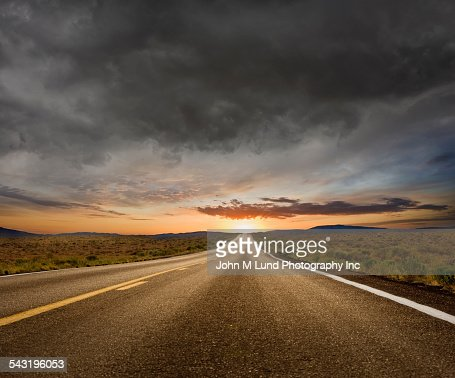 Empty road under sunset sky in remote landscape