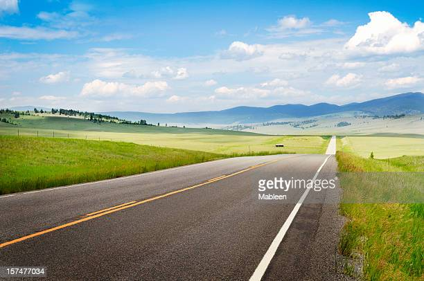 Empty road with fields on both sides in Montana