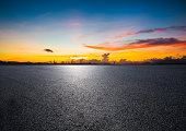 empty road with panoramic cityscape at sunset