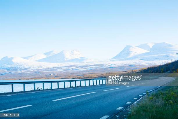 Empty road with snowcapped mountains on background