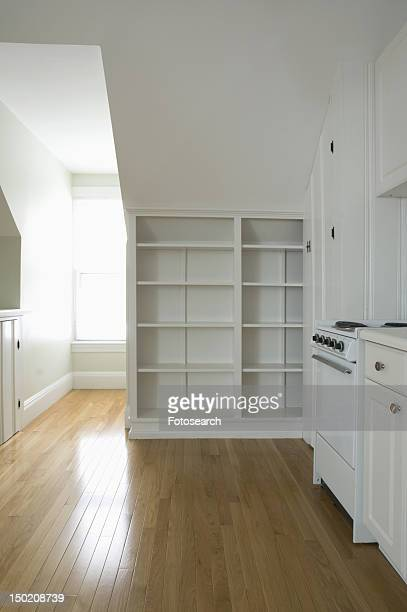 Empty room in apartment with hardwood floor and bookcase