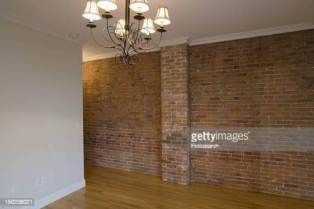Empty room in apartment with hardwood floor and brick wall
