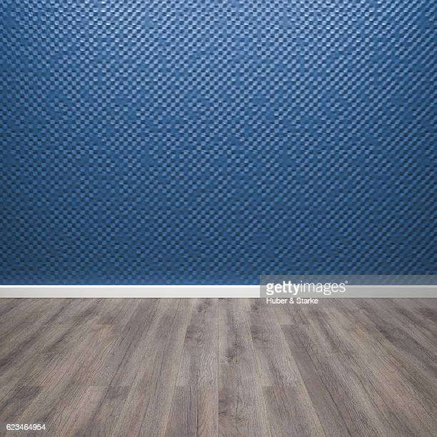Empty room with blue patterned wall and wooden floor