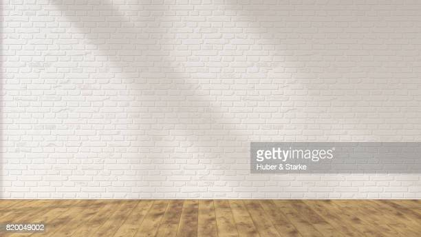 empty room with brick wall and hardwood floor