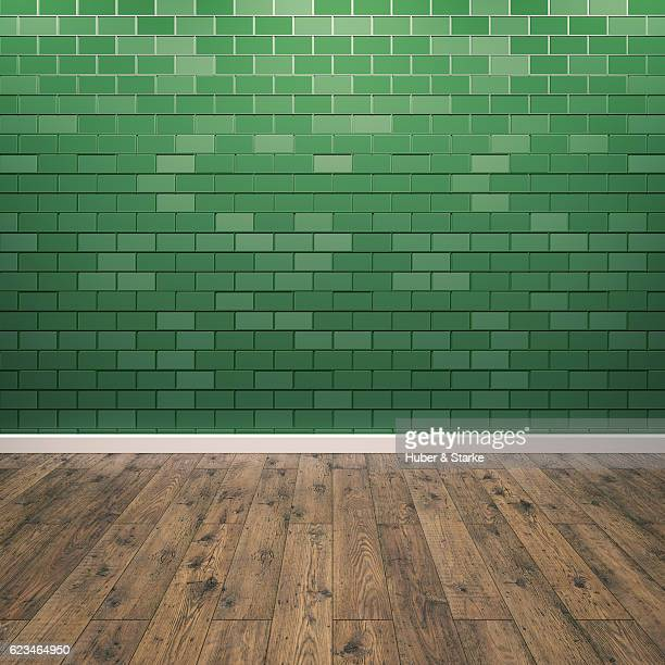 Empty room with green patterned wall and wooden floor