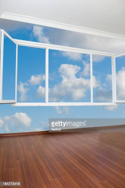 Empty room with mural of blue sky, white clouds and a window