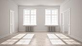 Empty room with parquet floor, big windows, doors and radiators, white interior design