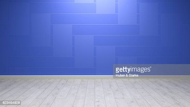 Empty room with patterned blue wall and wooden floor