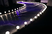 Empty Runway Fashion Show with Ball glowing lighting along walk way with plastic white floor in the dark