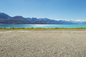 empty rural road near lake and snow mountain in new zealand